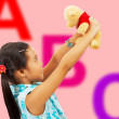 Girl Holding Her Teddy Bear Up In The Air — Stock Photo