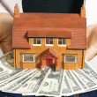 A person holding a miniature house and some dollar bills — Stock Photo