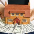A person holding a miniature house and some dollar bills - ストック写真