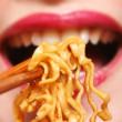 Young chinese woman eating noodles - Stock Photo