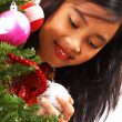 Girl Adding Balls To A Christmas Tree — Stock Photo #6439790