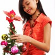 Girl Adding Tinsel To A Christmas Tree — Stock Photo