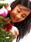 Dziewczyna dodając kulki na choinkę — Zdjęcie stockowe
