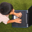 Stock Photo: Young Kid Using His Notebook Computer