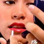 Girl Applying Lip Gloss Using A Mirror — Stock Photo