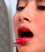 Woman Looking In The Mirror And Applying Lipstick — Stock Photo