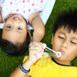 Two Kids Lying And Playing On The Grass — Stock Photo