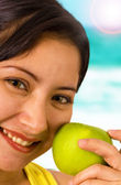 Young Smiling Lady At The Beach Holding An Apple — Stock Photo