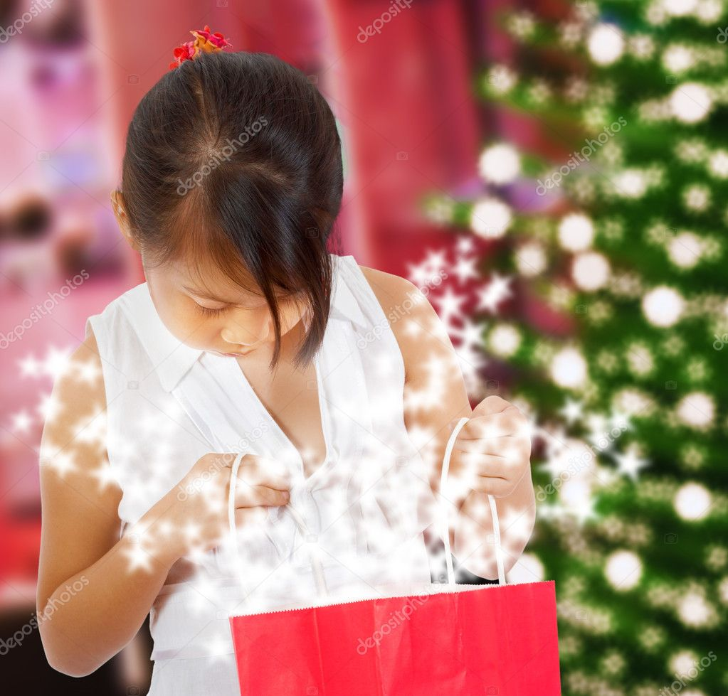 Excited Girl Looking At Her Sparkling Christmas Gift Ny The Xmas Tree — Stock Photo #6670689