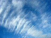Blue sky background with fleecy clouds — Stock Photo