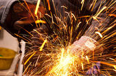 Worker cutting metal with many sharp sparks — Stock Photo