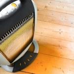 Halogen or infra heater in action against wooden floor — Stock Photo #5682974