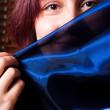 Stock Photo: Girl holding blue scarf before her face