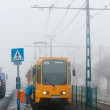 New tram with passanger getting on in the fog - Stock Photo