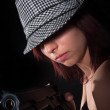 Girl with hat pointing gun - Stock Photo