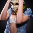 Stock Photo: Girl in gasmask holding her head