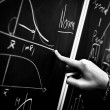 Pointing on chalk board in black and white — Stock Photo