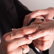 Groom putting a ring on bride's finger during wedding ceremony — Foto de Stock