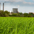 Stock Photo: Green field with Industry in background polluting our beauti