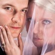 Young bride in veil holding the chin of the groom — Stock Photo #5683383