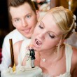 Young bride is going to bite her cake with groom in background — Stock Photo