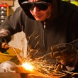 Worker welding with hot flame and sparks - Stock Photo