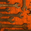 Many rusty spanners on wooden board - Stock Photo
