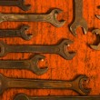 Royalty-Free Stock Photo: Many rusty spanners on wooden board