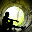 Silhouette of a young girl smoking in sewer pipe - Stock Photo