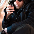 Hooded man looking at his cellular phone in an old airplane — Stock Photo