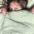 Portrait of a young girl hiding under blanket — Stock Photo
