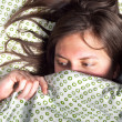 Young scared girl hiding under blanket — Stock Photo