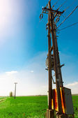 Power line against blue sky on green field — Stock Photo