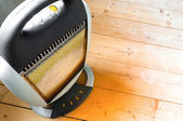 Halogen or infra heater in action against wooden floor — Stock Photo