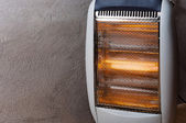 A halogen or electric heater against concrete wall — Stock Photo