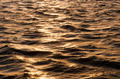 Waves of water reflecting the sunset — Stock Photo