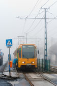 New tram with passanger getting on in the fog — Stock Photo