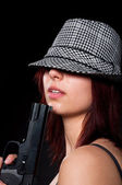 Beautiful young girl in hat holding pistol — Stock Photo