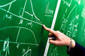 緑の黒板を指さし学生の手 — ストック写真