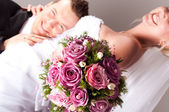 Young couple in wedding wear with bouquet of roses — Stock Photo