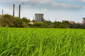 Green field with Industry in the background polluting our beauti — Stock Photo