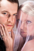 Young bride in veil holding the chin of the groom — Stock Photo