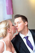 Handsome groom kissing her bride — Photo