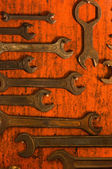 Many rusty spanners on wooden board — Stock Photo