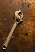 Adjustable wrench on rusty metal plate — Foto Stock