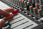 Part of an audio sound mixer with buttons and sliders and hand — Stock Photo