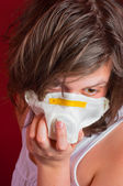 Girl wearing protective mask against red background — Stock Photo