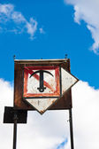 Rusty sign with boat anchor against blue sky — Stock Photo