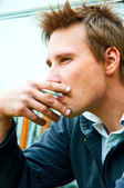 Closeup of a young man with cigarette in mouth — Stock Photo