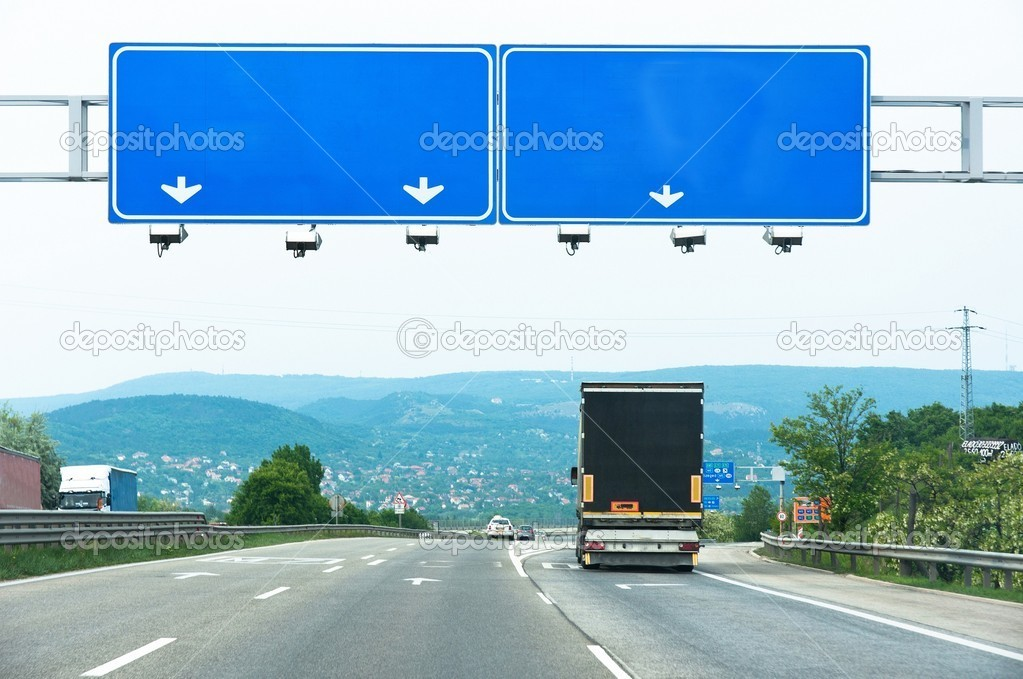 Big blue sign on highway with truck and car — Stock Photo #5684328
